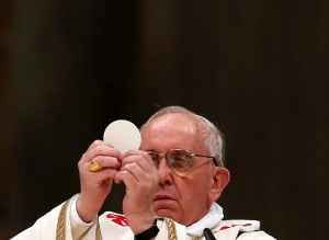Pope Francis elevates the host as he leads a vigil mass during Easter celebrations at St. Peter's Basilica in the Vatican