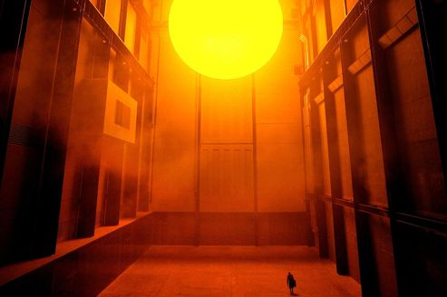 A WOMAN IS SILHOUETTED UNDER A GIANT 'SUN' IN THE TURBINE HALL ATLONDON'S TATE MODERN ART GALLERY.