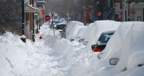 Parked cars along a street buried in snow