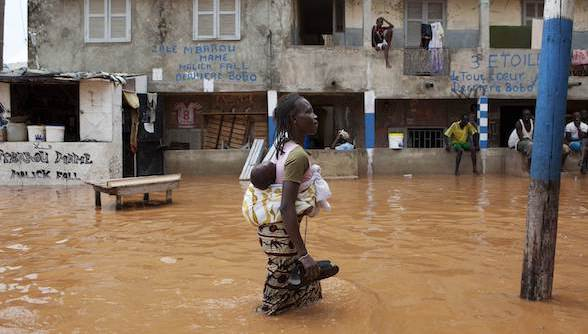 A woman with a baby on her back wades through water after overnight flooding on a street in Dakar